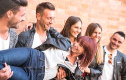 Multicultural guys and girls millennial holding female friend an. D having genuine fun at brick stone wall in the city - Urban youth concept with young people stock photography