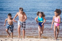 multicultural happy children in swimsuits running stock photos