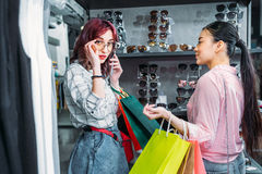 Multicultural hipster girls choosing sunglasses in boutique. Friends shopping concept concept Royalty Free Stock Images