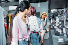 Multicultural hipster girls choosing sunglasses in boutique. Friends shopping concept concept Royalty Free Stock Photos