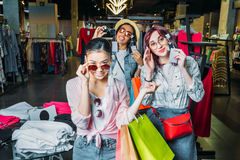 Multicultural hipster girls choosing sunglasses in boutique. Friends shopping concept concept Stock Image