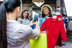 Multicultural hipster girls taking photo in boutique. Fashion shopping girls concept Royalty Free Stock Photo