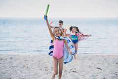 multicultural kids in towels with water toys in hands running royalty free stock photos