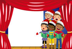Multicultural kids wearing xmas hat singing Christmas carol nativity play stage copyspace Stock Photos