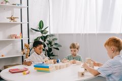 Multicultural little boys plying with wooden blocks at table. In classroom royalty free stock photography