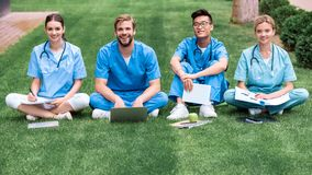 Multicultural medical students sitting on grass and looking. At camera royalty free stock photos