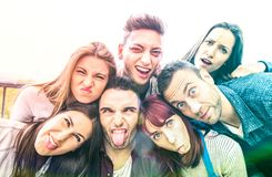 Multicultural millenial friends taking selfie with funny faces - Happy youth friendship concept with millennial young trends royalty free stock photo