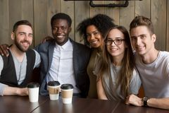 Multicultural millennial young friends looking at camera in cafe. Portrait of multicultural millennial young friends looking at camera, happy multiracial people Stock Image