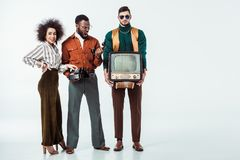 multicultural retro styled friends holding vintage television and telephone royalty free stock photography