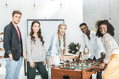 multicultural smiling business people looking at camera while playing table football stock images