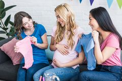 Multicultural smiling women choosing baby clothes with pregnant friend. Baby-party concept royalty free stock photography