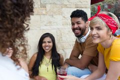 Multicultural students bonding and drinking at restaurant outside. Summer, warm, friendship, diversity, reunion concept. Young adults having a great time at cafe royalty free stock photo