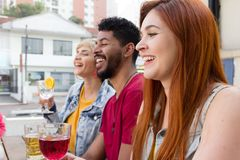 Multicultural students partying together at cafe bar outdoor. Spring, warm, togetherness, lifestyle, diversity concept. Young adults hanging out, having fun at royalty free stock photography
