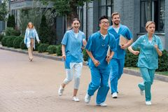 Multicultural students running near medical. University stock photos