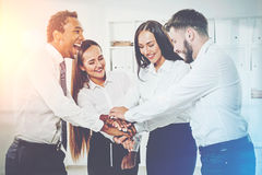 Multicultural team of colleagues in an office with hands togethe Royalty Free Stock Images