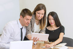 Multicultural team looking at a tablet stock photography