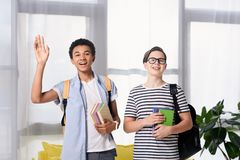 Multicultural teen boys greeting someone. At home stock photos