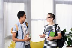 Multicultural teen boys holding books and talking. At home stock photo