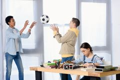 Multicultural teen boys playing with football ball while female teenager fixing circuit. At home stock photography