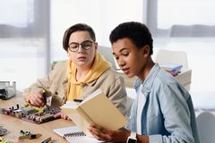 Multicultural teen boys reading book about soldering motherboard. At home royalty free stock photo