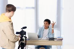 Multicultural teen boys shooting video blog with camera. At home stock photo