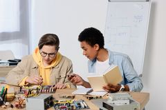 Multicultural teen boys studying and repairing computer motherboard. At home royalty free stock photography