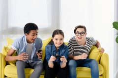 Multicultural teen boys supporting friend playing video game. At home stock images