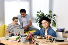 Multicultural teen boys using laptop and female kid fixing computer motherboard. At home royalty free stock photo