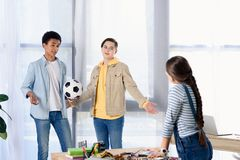 Multicultural teenagers holding football ball and looking at friend. At home stock photos