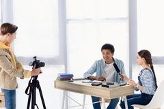 Multicultural teenagers shooting video blog about engineering. At home royalty free stock photography