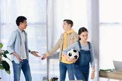 Multicultural teenagers showing shrug gestures while friends walking away with football ball. At home royalty free stock photo
