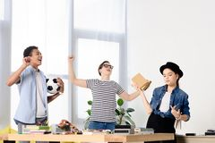Multicultural teenagers showing yes gestures and holding football ball. At home stock image