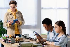 Multicultural teenagers soldering computer circuit with soldering iron and friend. Reading book stock photo