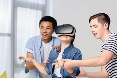 Multicultural teenagers supporting friend with virtual reality headset. At home stock photo
