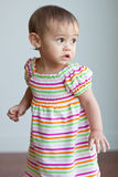 Multicultural toddler girl in cute dress. A one year old toddler girl is standing up and looks outside with her big brown eyes.  She has brown hair and is Stock Images
