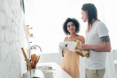 Multicultural young couple washing dishes and looking. At each other royalty free stock photos