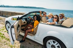Multicultural young friends sitting in car and looking at camera. At seaside royalty free stock photography