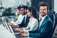 Multicultural young happy employees in call center. Sitting at computers and working. Teamwork. Employees in headset royalty free stock image