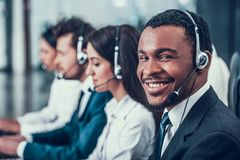 Multicultural young happy employees in call center. Sitting at computers and working. Teamwork. Employees in headset stock photo
