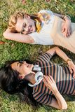 multicultural young smiling women resting on green grass stock images