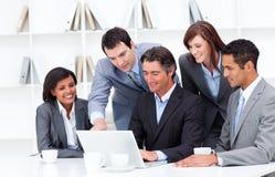 Multicultureel commercieel team dat laptop bekijkt royalty-vrije stock afbeelding