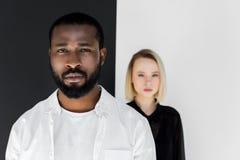multicultureel paar die camera dichtbij zwart-witte muur bekijken yin royalty-vrije stock foto's