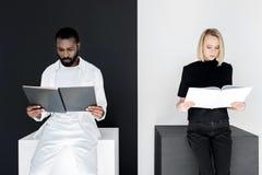 multicultureel paar die zwart-witte boeken lezen yin stock foto