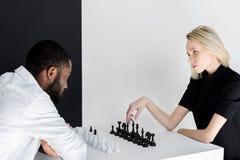 multicultureel paar het spelen schaak dichtbij zwarte royalty-vrije stock afbeeldingen