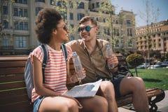 multicultureel paar van reizigers met kaart en fles water het rusten royalty-vrije stock foto's