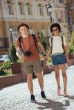 multicultureel paar van toeristen met camera en kaart die en handen van elk lopen houden stock afbeeldingen