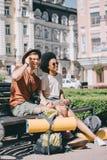multicultureel paar van toeristen met rugzakken en matten het rusten royalty-vrije stock foto's