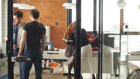 Multicultureel team van actieve bedrijfsmensen die in goede stemming doorbrengend tijd genieten van stock footage