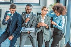 multicultureel zakenlui met koffiekrant en smartphone stock afbeelding