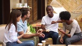 Multiculturele gelukkige vrienden die etend pizza in restaurant openlucht lachen stock footage